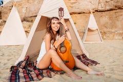 Het glimlachen het jonge hippievrouw stellen met gitaar bij het strand Royalty-vrije Stock Foto's