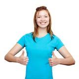Het glimlachen het jonge vrouw omhoog beduimelt tonen stock foto's