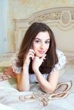 Het glimlachen het jonge vrouw spreken mobiel in haar slaapkamer Stock Afbeeldingen