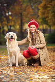 Het glimlachen het jonge vrouw stellen met labrador retriever   Stock Fotografie