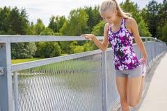 Het glimlachen het jonge vrouw uitrekken zich openlucht op een brug Stock Afbeeldingen