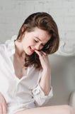 Het glimlachen het lachen vrouwenportret die - op stoelbank rusten in man vriend wit overhemd thuis in ochtendlevensstijl Stock Foto's