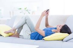 Het glimlachen het mooie donkerbruine ontspannen op de laag en het gebruiken van haar telefoon Royalty-vrije Stock Afbeelding
