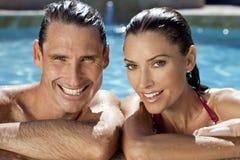 Het glimlachen het Ontspannen van het Paar in Zwembad Stock Afbeeldingen
