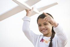 Het glimlachen het Spaanse meisje spelen met stuk speelgoed modelvliegtuig royalty-vrije stock fotografie