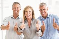 Het glimlachen het toevallige bedrijfsmensen omhoog beduimelt doen Royalty-vrije Stock Foto