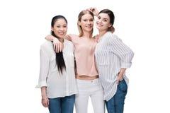 Het glimlachen het toevallige meisjes omhelzen geïsoleerd op wit Royalty-vrije Stock Foto's