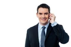 Het glimlachen het uitvoerende spreken via mobiele telefoon Stock Afbeeldingen