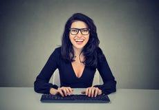 Het glimlachen het verbaasde vrouw typen op een computertoetsenbord royalty-vrije stock afbeelding