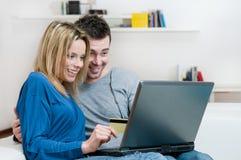 Het glimlachen het verraste paar online winkelen Stock Afbeeldingen