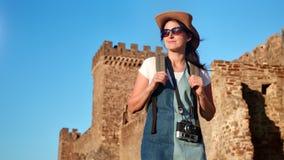 Het glimlachen hipster backpacker toeristenvrouw het ontspannen bij middeleeuws kasteel middelgroot schot als achtergrond stock videobeelden