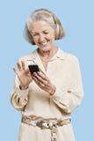 Het glimlachen hoger de tekstbericht van de vrouwenlezing op celtelefoon tegen blauwe achtergrond Stock Afbeeldingen