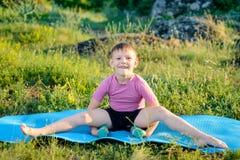 Het glimlachen Jong geitje het Opheffen Gewichten terwijl het Verdelen van Benen Stock Fotografie