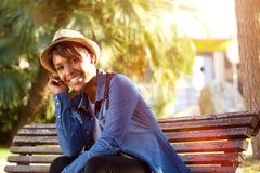 Het glimlachen jonge Afrikaanse Amerikaanse vrouwenzitting buiten Royalty-vrije Stock Foto's