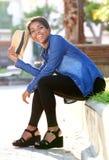 Het glimlachen jonge Afrikaanse Amerikaanse vrouwenzitting buiten Stock Afbeelding