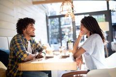 Het glimlachen jonge Afrikaanse paarzitting bij een lijst bij een koffie het drinken koffie en samen het spreken royalty-vrije stock foto's