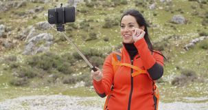 Het glimlachen jonge backpacker die een selfiestok gebruiken stock footage