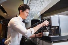 Het glimlachen jonge barista die kop van koffie maken royalty-vrije stock afbeeldingen
