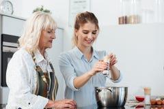Het glimlachen het jonge meisje koken samen met haar grootmoeder stock foto