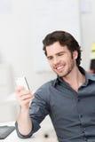 Het glimlachen jonge mens lezen sms op zijn mobiel Stock Foto's
