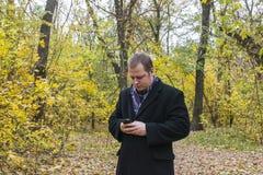 Het glimlachen jonge mensenlezing sms op telefoon Een mens controleert de post op de telefoon Royalty-vrije Stock Afbeeldingen