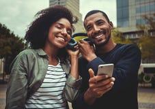 Het glimlachen het jonge paar genieten die aan muziek op één hoofdtelefoon luisteren stock afbeeldingen