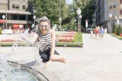 Het glimlachen het jonge vrouw bespatten met water stock afbeeldingen