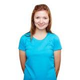 Het glimlachen jonge vrouw status Het blauwe concept van het t-shirtontwerp stock fotografie