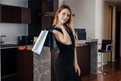 Het glimlachen het jonge vrouw stellen met het winkelen zak gelukkig met haar aankoop thuis royalty-vrije stock foto's