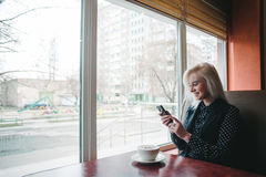 Het glimlachen jonge vrouwenzitting in een koffie dichtbij het venster met een kop van koffie royalty-vrije stock fotografie