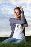 Het glimlachen jonge vrouwenzitting in het gras wat betreft haar haar Royalty-vrije Stock Afbeelding