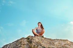 Het glimlachen jonge vrouwenzitting op de bovenkant van berg Royalty-vrije Stock Fotografie