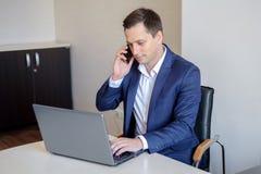 Het glimlachen jonge zakenmanzitting achter zijn bureau met laptop en het spreken op mobiele telefoon in bureau Royalty-vrije Stock Foto's