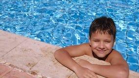 Het glimlachen jongen het ontspannen op zwembad stock video