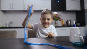 Het glimlachen jongen het spelen met lang met de hand gemaakt slijm stock videobeelden