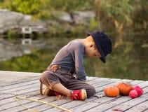 Het glimlachen jongenszitting met Halloween-pompoenen Royalty-vrije Stock Foto