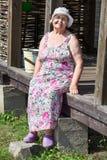 Het glimlachen Kaukasische hogere grandwoman zitting op houten portiek royalty-vrije stock fotografie