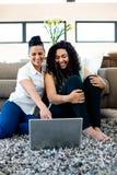 Het glimlachen lesbische paarzitting op deken en het gebruiken van laptop Stock Afbeeldingen