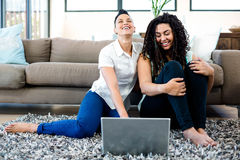 Het glimlachen lesbische paarzitting op deken en het gebruiken van laptop Stock Foto