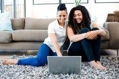 Het glimlachen lesbische paarzitting op deken en het gebruiken van laptop Royalty-vrije Stock Foto