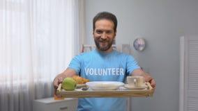 Het glimlachen mannelijk vrijwilligers tonend dienblad op middelbare leeftijd met ontbijt aan camera, zorg stock footage