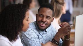 Het glimlachen mannelijke Afrikaanse werknemer het luisteren vrouwelijke collegazitting in bureau stock videobeelden