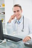 Het glimlachen mannelijke artsenzitting met computer op medisch kantoor royalty-vrije stock afbeelding