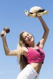 Het glimlachen maracas en de hoed van de meisjesholding in lucht Stock Foto's
