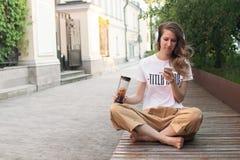 Het glimlachen meisje het ontspannen bij straat, speelt zij muziek gebruikend een smartphone en dragend witte hoofdtelefoons stock fotografie