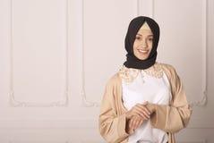 Het glimlachen meisjes oostelijke verschijning in Moslimkleding en een sjaal op haar hoofd op een klassieke lichte achtergrond stock afbeeldingen