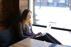 Het glimlachen meisjeszitting dichtbij lijst met notitieboekje en holdingskop van cappuccino stock foto's