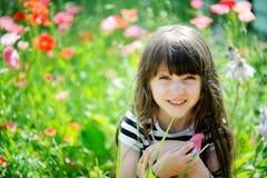 Het glimlachen meisjezitting op papavergebied Stock Foto