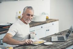 Het glimlachen mens smakelijk eten omfloerst voor ontbijt royalty-vrije stock fotografie