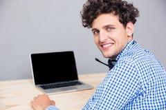 Het glimlachen mensenzitting bij de lijst met laptop royalty-vrije stock foto's